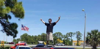 Jeff Kelly, an Army veteran, stands on top of his car. (Credit: WINK News)