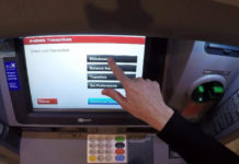 Person at an ATM. (Credit: CBS News)