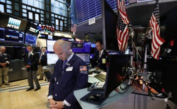 Traders pause for a moment of silence on the floor of the New York Stock Exchange, for the victims of the weekend shootings, Monday, Aug. 5, 2019. (AP Photo/Richard Drew)