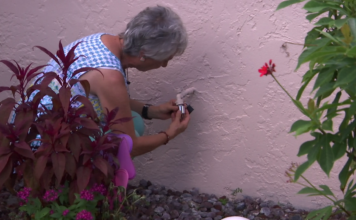 Jo-Ann Piacente installs a bibb lock on a water spigot at her Cape Coral home. (WINK News)