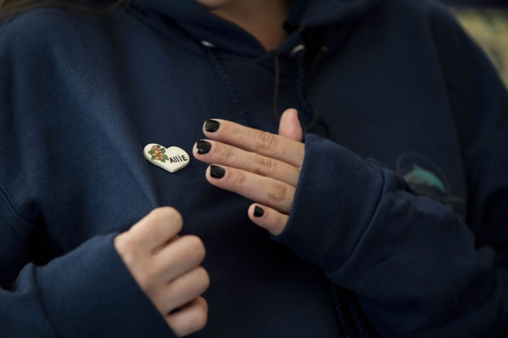 Olivia Kurtz wears a pin in memory of her sister Allie, who lost her life on the dive boat Conception, during at interview with The Associated Press on Wednesday, Sept. 4, 2019, in Santa Barbara, Calif. A fire raged through the boat carrying recreational scuba divers anchored near an island off the Southern California Coast Monday, leaving multiple people dead. (AP Photo/Christian Monterrosa)
