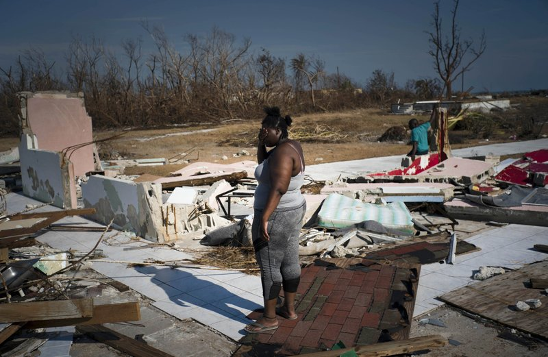 FILE: A woman is overcome as she looks at her house destroyed by Hurricane Dorian, in High Rock, Grand Bahama, Bahamas, Friday Sept. 6, 2019. The Bahamian health ministry said helicopters and boats are on the way to help people in affected areas, though officials warned of delays because of severe flooding and limited access. (AP Photo/Ramon Espinosa/FILE)