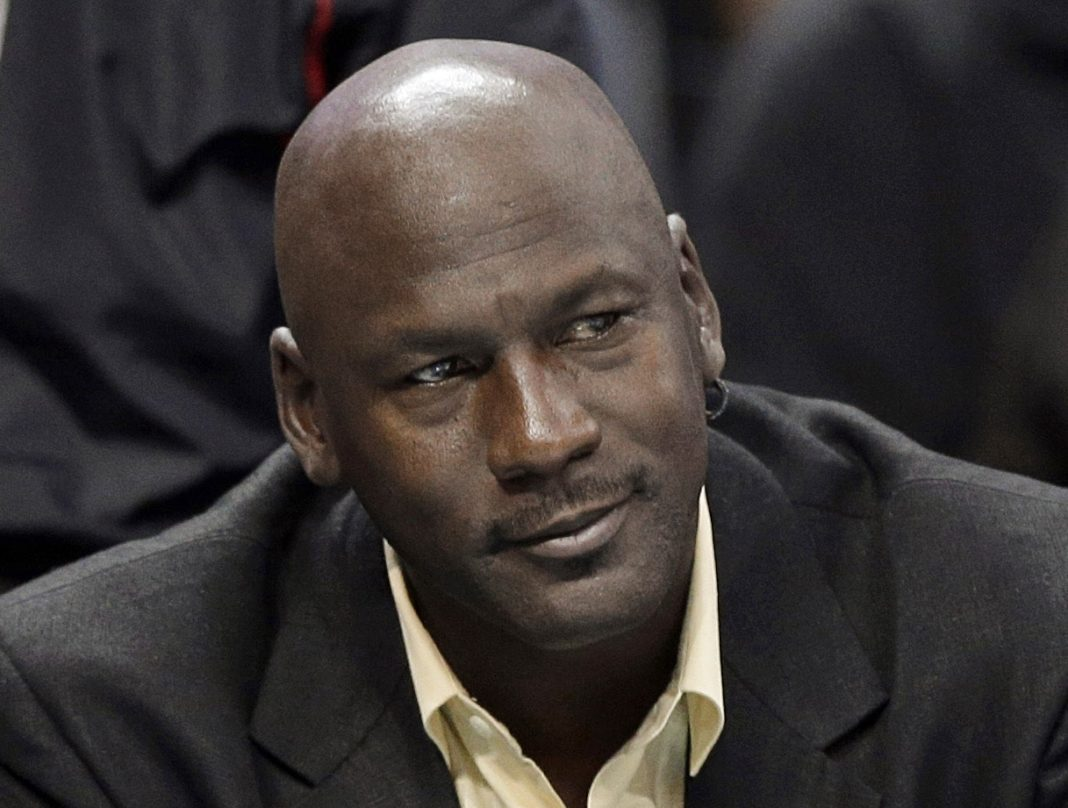 FILE - In this April 16, 2014, file photo, Charlotte Bobcats owner Michael Jordan watches an NBA basketball game between the Bobcats and the Chicago Bulls in Charlotte, N.C. The six-time NBA champion is scheduled to appear Tuesday, Aug. 11, 2015, in federal court in Chicago for the start of a civil trial and will later testify on the unauthorized use of his identity. A court already ruled a grocery-story chain used his identity without permission in a magazine ad and so the unresolved legal issue is damages. (AP Photo/Chuck Burton, File)