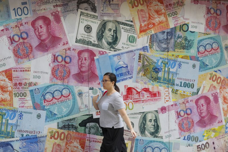 FILE - In this Aug. 6, 2019, file photo, a woman walks by a money exchange shop decorated with different countries currency banknotes at Central, a business district in Hong Kong. The Hong Kong stock exchange is dropping a bid to buy its London counterpart following opposition from the European exchange's management. Hong Kong Exchanges and Clearing Ltd. said it was