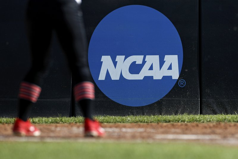 FILE - In this April 19, 2019, file photo, an athlete stands near a NCAA logo during a softball game in Beaumont, Texas. The NCAA is poised to take a significant step toward allowing college athletes to earn money without violating amateurism rules. The Board of Governors will be briefed Tuesday, Oct. 29 by administrators who have been examining whether it would be feasible to allow college athletes to profit of their names, images and likenesses. A California law set to take effect in 2023 would make it illegal for NCAA schools in the state to prevent athletes from signing personal endorsement deals. (AP Photo/Aaron M. Sprecher, File)