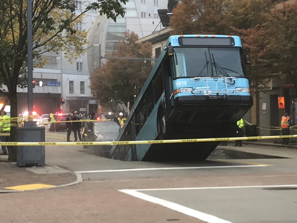 Authorities investigate after a Port Authority bus was caught in a sinkhole in downtown Pittsburgh on Monday, Oct. 28, 2019. The Port Authority of Allegheny County says the lone passenger is being treated Monday morning for minor injuries. (Darrell Sapp/Pittsburgh Post-Gazette via AP)