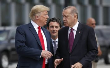 FILE - In this Wednesday, July 11, 2018, file photo, President Donald Trump, left, talks with Turkey's President Recep Tayyip Erdogan, as they arrive together for a family photo at a summit of heads of state and government at NATO headquarters in Brussels. The White House says Turkey will soon invade Northern Syria, casting uncertainty on the fate of the Kurdish fighters allied with the U.S. against in a campaign against the Islamic State group. (AP Photo/Pablo Martinez Monsivais, File)