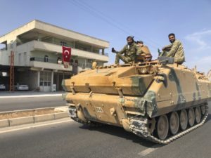 In this Friday, Oct. 18, 2019 photo, Turkish-backed Syrian opposition fighters ride atop their armored personnel carrier to cross the border into Syria, in Akcakale, Sanliurfa province, southeastern Turkey. (AP Photo/Mehmet Guzel)