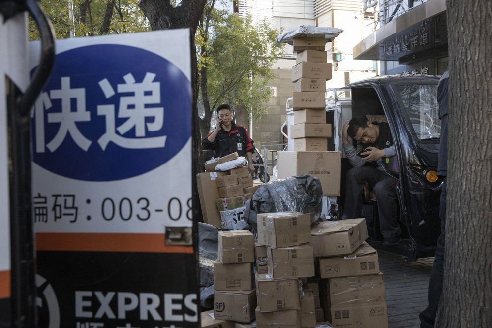 Delivery men wait to distribute parcels on the streets of Beijing on Monday, Nov. 11, 2019. Chinese e-commerce giants Alibaba and JD.com reported a total of more than $50 billion in sales on Monday in the first half of Singles Day, an annual marketing event that is the world's busiest online shopping day. The sign reads