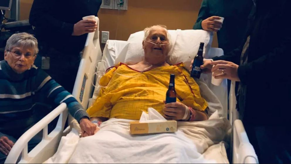In a heartwarming photo that has now gone viral, Norbert Schemm was pictured with his sons having a beer inside a hospital room a day before his death. (Credit: CBS News)