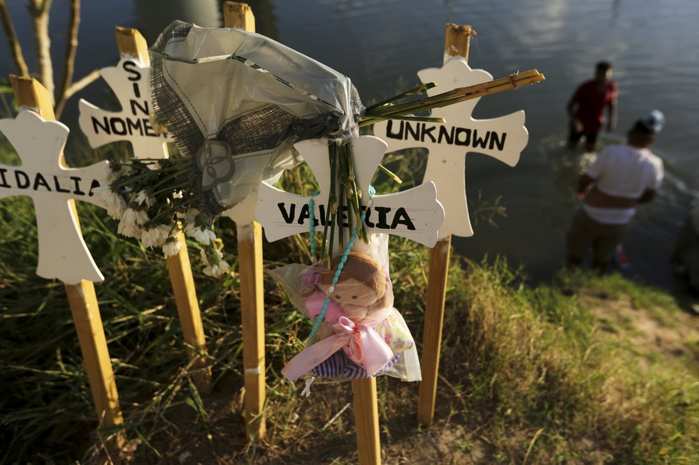 In this Oct. 11, 2019 photo, crosses covered with the names of people who have drowned trying to cross the river stand on the bank of the Rio Grande in Matamoros, Mexico. Migrants who make it this far, tell stories of being captured by armed bandits who demand a ransom: They can pay for illegal passage to the border, or merely for their freedom, but either way they must pay. (AP Photo/Fernando Llano)