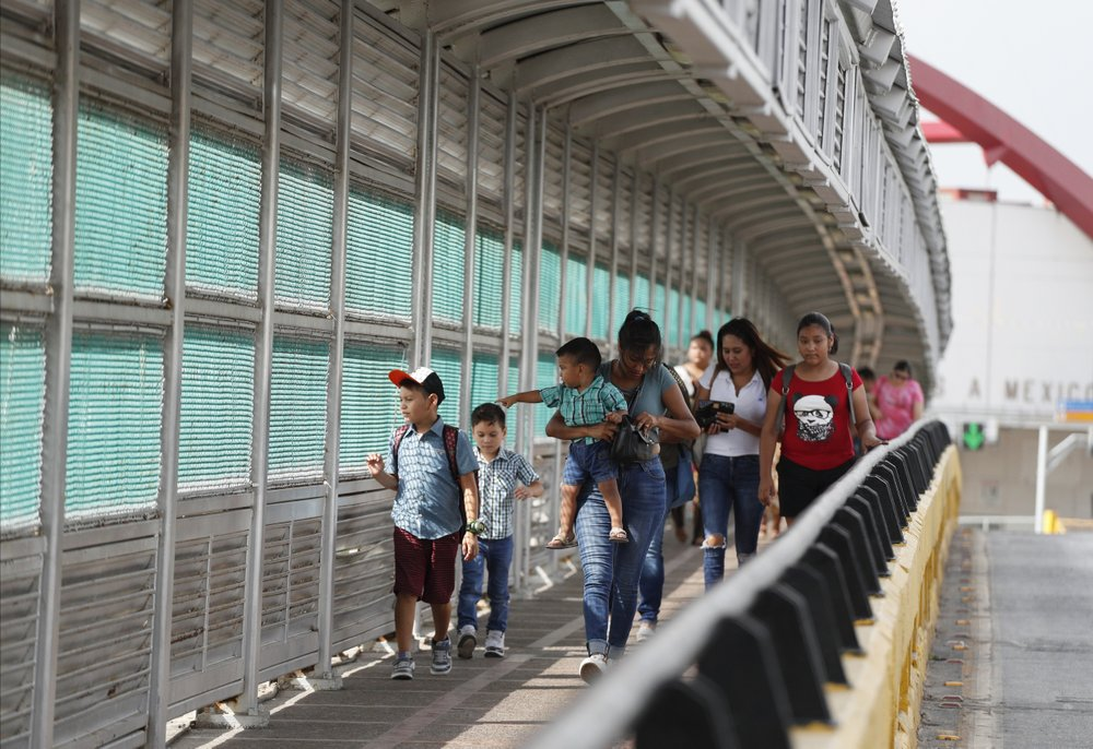 FILE - In this June 28, 2019 file photo, local residents with visas walk across the Puerta Mexico international bridge to enter the U.S., in Matamoros, Tamaulipas state, Mexico. A federal judge in Portland, Ore., on Saturday, Nov. 2, 2019, put on hold a Trump administration rule requiring immigrants prove they will have health insurance or can pay for medical care before they can get visas. U.S. District Judge Michael Simon granted a preliminary injunction that prevents the rule from going into effect Sunday. (AP Photo/Rebecca Blackwell, File)