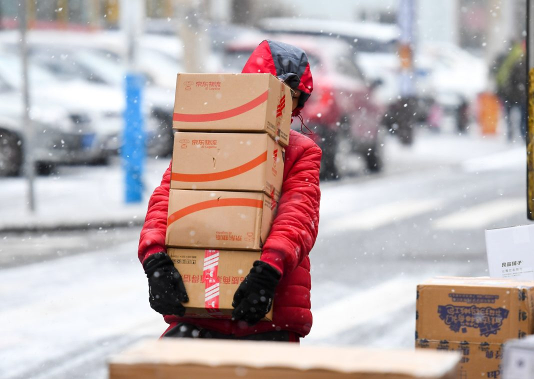 A JD.com employee carries parcels in snow on November 13, 2019 in Changchun, Jilin Province of China. (Credit: VCG via Getty Images)
