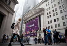 Pedestrians pass in front of a Slack Technologies Inc. signage displayed outside of the New York Stock Exchange (NYSE) during the company's initial public offering (IPO) in New York, U.S., on Thursday, June 20, 2019. (Credit: Michael Nagle/Bloomberg/Getty)