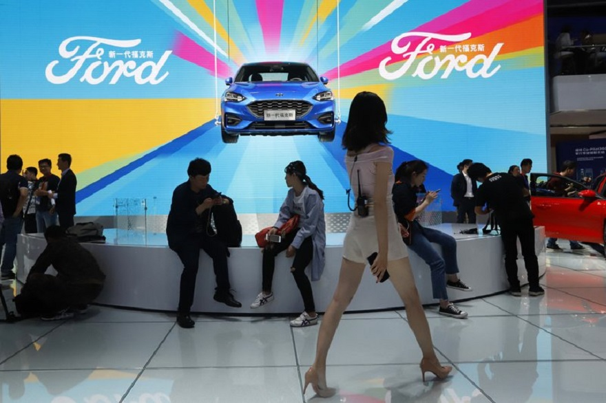 FILE - In this April 25, 2018, file photo, attendees visit the Ford booth during Auto China 2018 show held in Beijing, China. China's government says it will postpone planned punitive tariffs on U.S.-made automobiles and other goods following an interim trade deal with Washington. Sunday, Dec. 15, 2019's announcement came after Washington agreed to postpone a planned tariff hike on $160 billion of Chinese goods and to cut in half penalties that already were imposed. (AP Photo/Ng Han Guan, File)