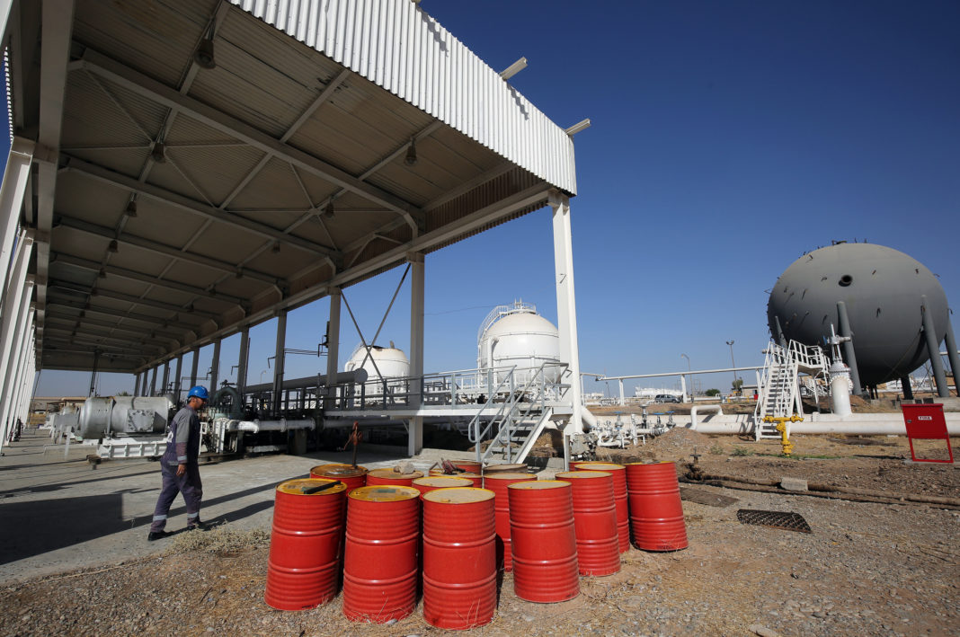 An Iraqi oil employee walks past oil barrels at the Bai Hassan oil field, west of the multi-ethnic northern Iraqi city of Kirkuk, on October 19, 2017. Kurdish peshmerga forces withdrew without a fight after federal government troops and militia entered Kirkuk, seizing the provincial governor's office and key military bases in response to a Kurdish vote for independence in September 2017. / AFP PHOTO / AHMAD AL-RUBAYE (Photo credit should read AHMAD AL-RUBAYE/AFP via Getty Images)