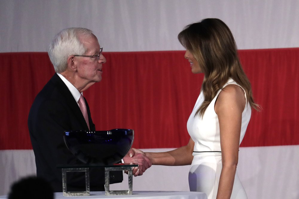 First lady Melania Trump, right, shakes hands with Palm Beach Atlantic University President Bill Fleming, left, after receiving the