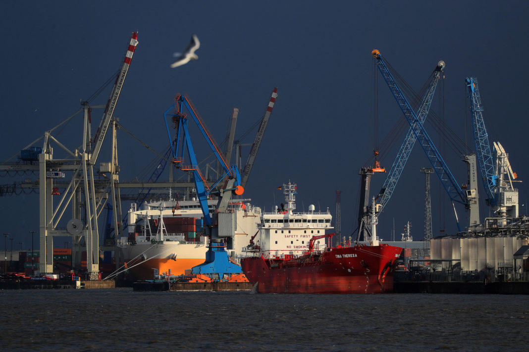Chemical and oil tanker Tina Theresa, right, sits docked near shipping cranes at the port of Hamburg in Hamburg, Germany, on Wednesday, Feb. 12, 2020. Germany's biggest bank has given the strongest warning yet that the nation is close to a recession as the coronavirus outbreak exacerbates its long-running industrial slump. Photographer: Krisztian Bocsi/Bloomberg via Getty Images